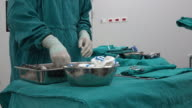 scrub nurse preparing surgical instruments for operation