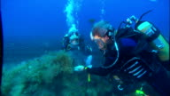 A scuba diver hammers away at volcanic rock then hands a piece to another diver who is watching. Available in HD.