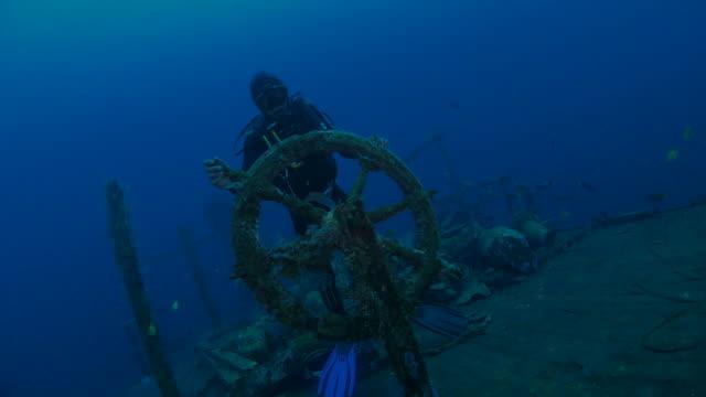 Scuba diver handling the rudder of Boga Shipwreck, Northern Bali