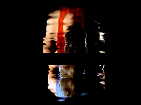 New video installation Video art installation by Bill Viola entitled 'Surrender' two figures one in blue and one red seen only in reflection bend and...