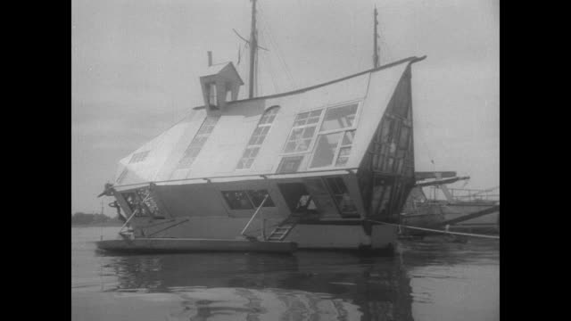 Sculptor David Brooks parks his new artsy houseboat in Oakland Estuary / various views of the boat 'new Moon' constructed out of a World War II...