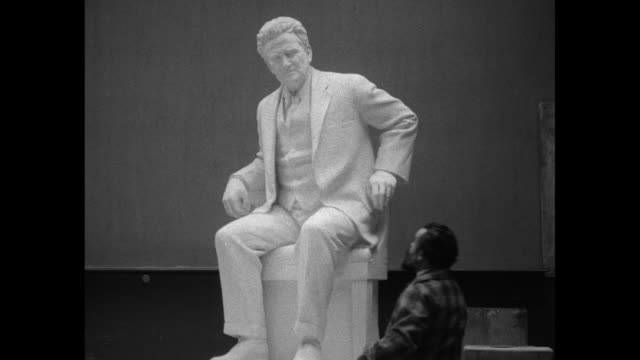 Sculptor Jo Davidson displays plaster likeness of the late US Sen Robert La Follette Sr as Robert La Follette Jr looks on / Note exact month/day not...