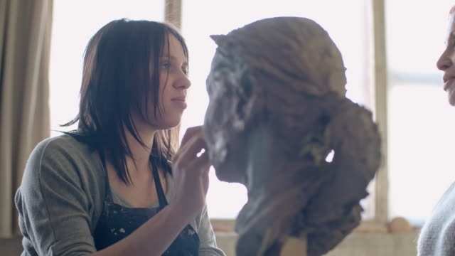 Sculptor working with live model
