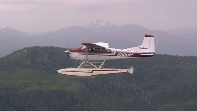 'Sea plane flying over evergreen forests, shot from adjacent sea plane, Revillagigedo Island, Alaska.'