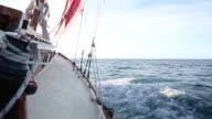 Sea spraying on deck of classic sailing yacht, early morning sail.