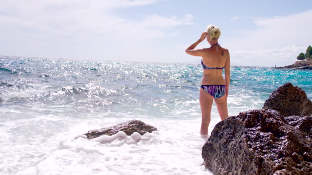 SLO MO Sea Waves Splashing Against Attractive Woman