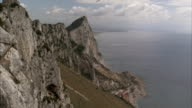 Seagulls circle a mountain towering over the sea. Available in HD
