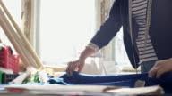 Seamstress drawing around pattern on blue fabric