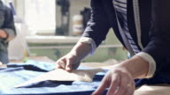 Seamstress outlining sewing pattern on fabric