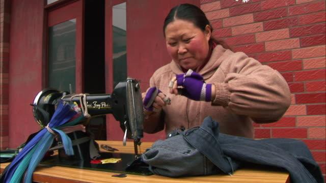 MS Seamstress smiling as she sits at sewing machine and works on pair of pants/ Guiyang, China