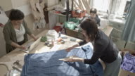 Seamstress with daughter and her colleague working in sewing workshop