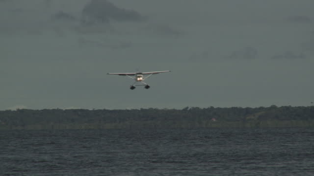 A seaplane lands on the ocean.