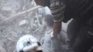 Search and rescue team members work at the destroyed area to remove bodies and survivors from the rubble after Syrian regime helicopters have shelled...