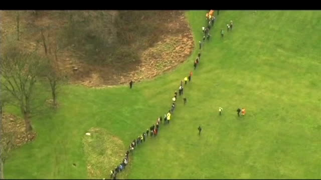 Search for missing boy Mikaeel Kular continues AERIAL people searching in line along grass area by coast