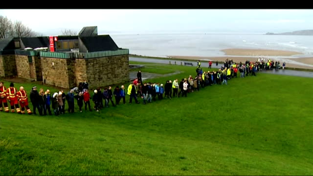 Search for missing boy Mikaeel Kular continues People in line searching grass area next to coast