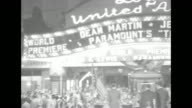 Searchlight sweeps exterior of Lowe's Ohio theater / lighted marquee 'Dean Martin Jerry Lewis Paramount's 'The Caddy' World Premiere'' and Martin and...