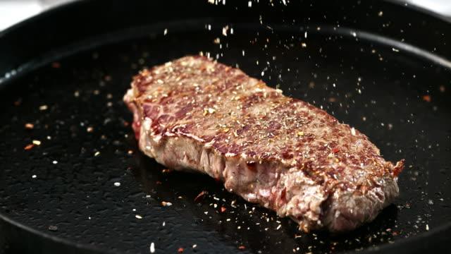 SLO MO Würzzutaten ein gebratenes Rindersteak