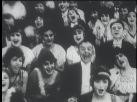 B/W 1915 seated audience in formalwear laughing