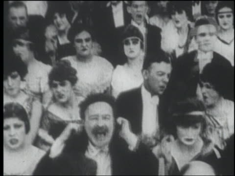 B/W 1915 seated audience in formalwear plugging ears + holding noses
