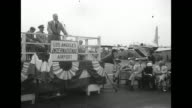 Seated dignitaries automobile beyond with crowd standing behind railing above / stage decorated with bunting and man speaking / Virginia Gibson / PAN...