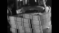 / Seated female worker stacks freshly printed and cut one dollar bills / male workers stack wrapped bundles of silver certificates / man shakes his...