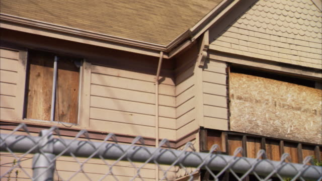 Second story of boarded up house w/ top of chainlink fence in FG Foreclosure Poverty Poor