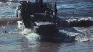 Secondwave Marines exiting a landing craft to shore wading through shallows carrying crates and driving Jeep down ramp to beach during World War II...