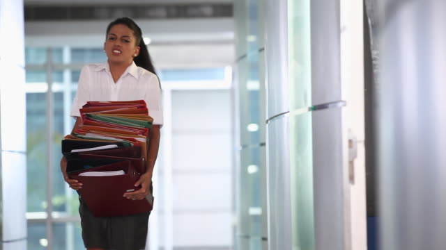 Secretary carrying a stack of files