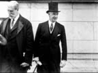 Secretary of State Charles Evans Hughes w/ unidentified man BG MS Group of men outside hall TU WS Flags of attending nations hanging over roof edge...