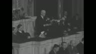 Secretary of State Cordell Hull stands before bank of radio microphones as he addresses a joint session of Congress about his attendance at the Third...
