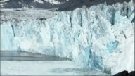 A section of ice falls into the bay as a glacier calves. Available in HD.