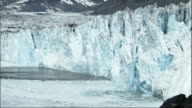 A section of ice falls into the bay near Columbia Glacier Alaska. Available in HD.