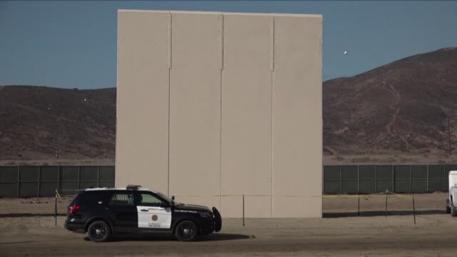 Sections of wall made of concrete and steel some with spikes on their tips stand near the Mexico US border