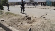 Security force members stand guard during the scene investigation and cleaning works at the roadside bomb blast site on the outskirts of Kabul...