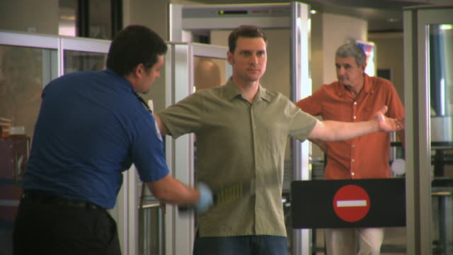MS Security guard checking passenger with metal detector, Appleton, Wisconsin, USA
