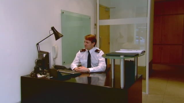 WS Security guard in uniform sitting at desk in office and looking at computer screen / London, England