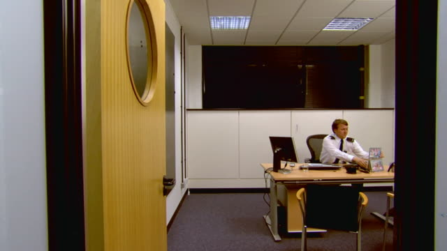 WS Security guard in uniform sitting in office and putting his feet up on desk / London, England