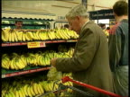 ENGLAND ITN MS Security guard opens Tesco supermarket doors and shoppers with trolleys towards amp in MS Man looking at prepacked dairy produce in...