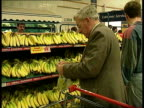 ENGLAND MS Security guard opens Tesco supermarket doors and shoppers with trolleys towards amp in MS Man looking at prepacked dairy produce in chill...