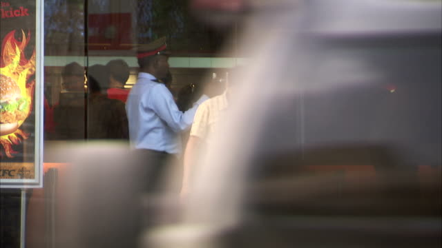 A security guard opens the door of a fast food restaurant in Jaipur.
