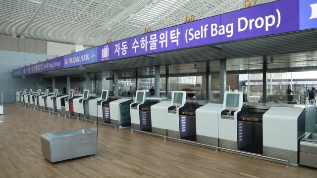 A security guard stands in front of a Korean Air Lines Co selfservice bag drop counter inside the nearly completed terminal 2 building during a media...