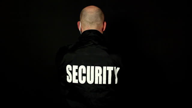 Security Guard turns around to face camera - Wide