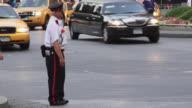 A security guard waits to cross the street at Columbus Circle.  Traffic navigates the circle and drives past