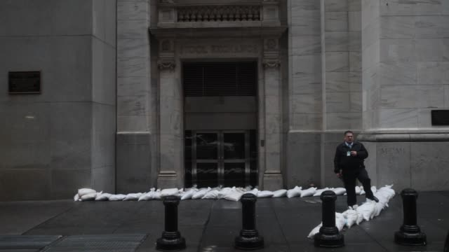 Security guard walks past sandbags in front of the closed New York Stock Exchange NYSE Closed Hurricane Sandy Prep on October 29 2012 in New York New...