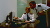 MS Security guard watching computer screen then another guard enters and takes seat at desk while other man leaves office / London, England