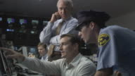 MS Security guard watching surveillance monitors with businessmen in television studio control room / Culver City, California, USA