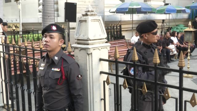 Security guards and people visit attend a religious ceremony at the Erawan Shrine four days after a bomb exploded close to the shrine in the center...