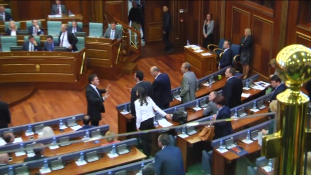 Security guards try to shield Kosovan Prime Minister Isa Mustafa with umbreallas as opposition lawmakers throwing eggs during his speech at the...