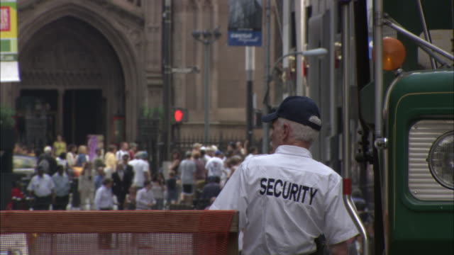 A security officer stands on  a busy New York City street.