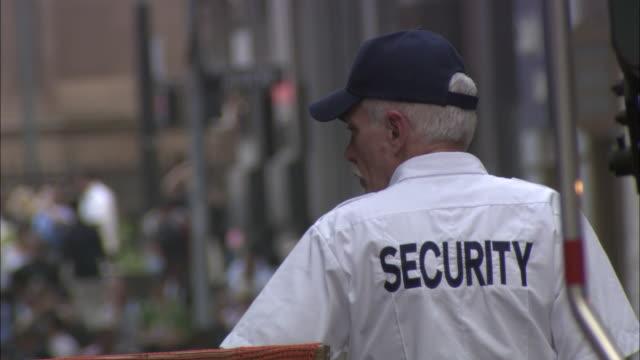 A security officer stands on a busy street as pedestrians pass.
